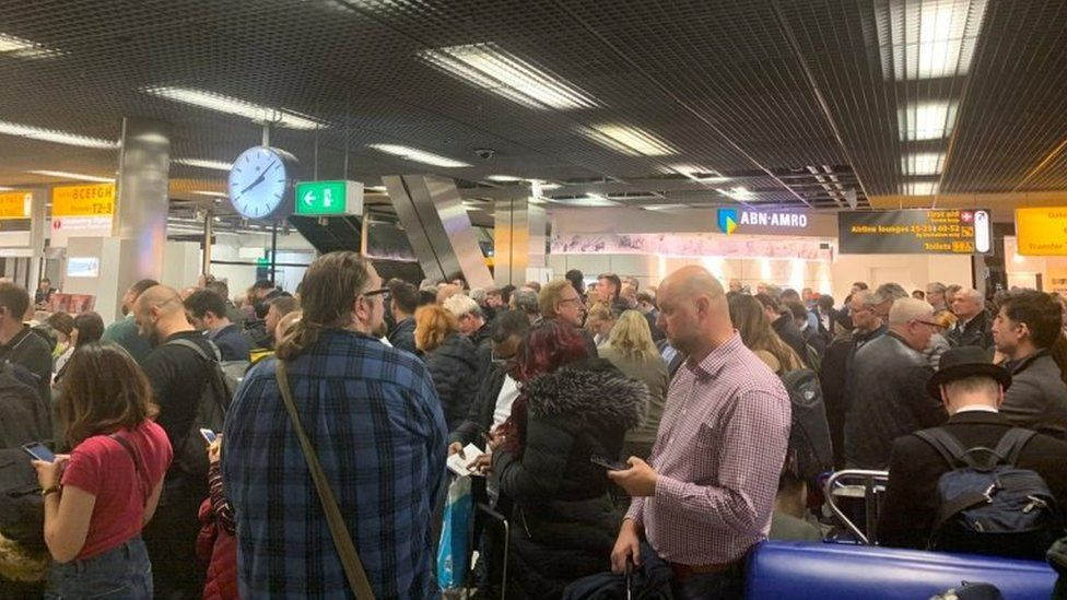 Passengers stand inside Amsterdam's Schiphol Airport during a security alert