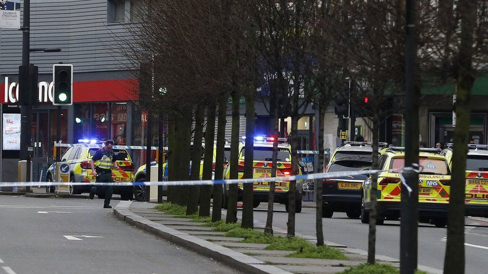 Police officers at the scene after a man was shot and killed by armed police