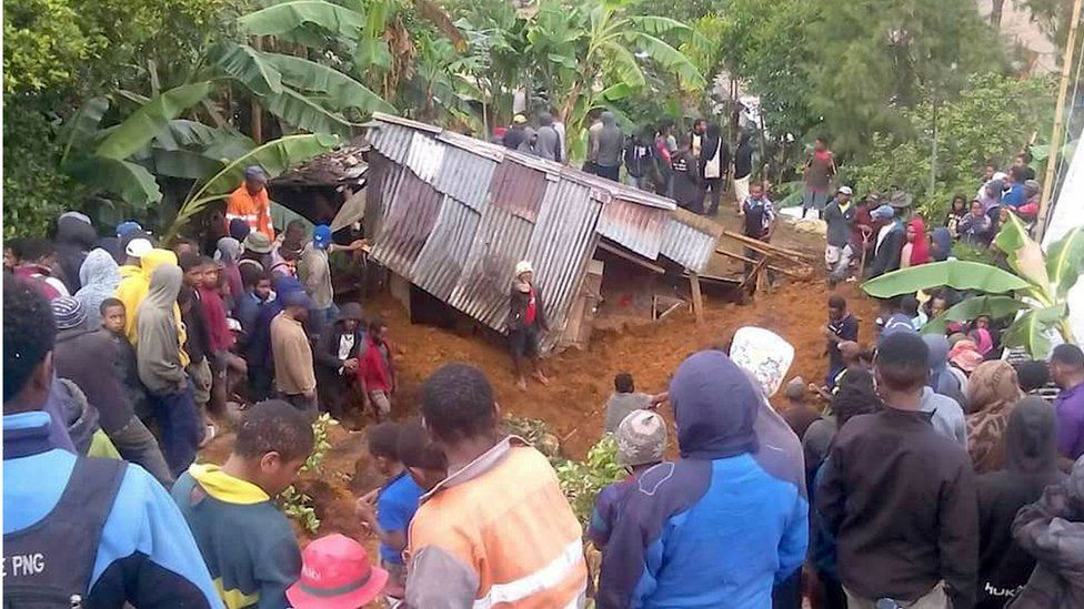 """Locals surround a house that was covered by a landslide in the town of Mendi after an earthquake struck Papua New Guinea""""s Southern Highlands in this image taken February 27, 2018"""