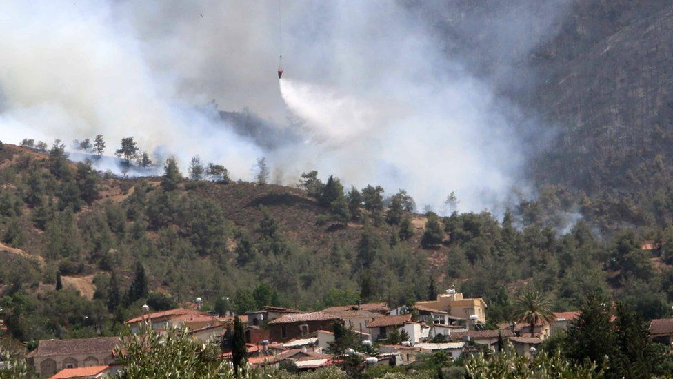A helicopter drops water on a forest fire in the village of Eyrixou in the Troodos mountain area, Cyprus, 20 June 2016.