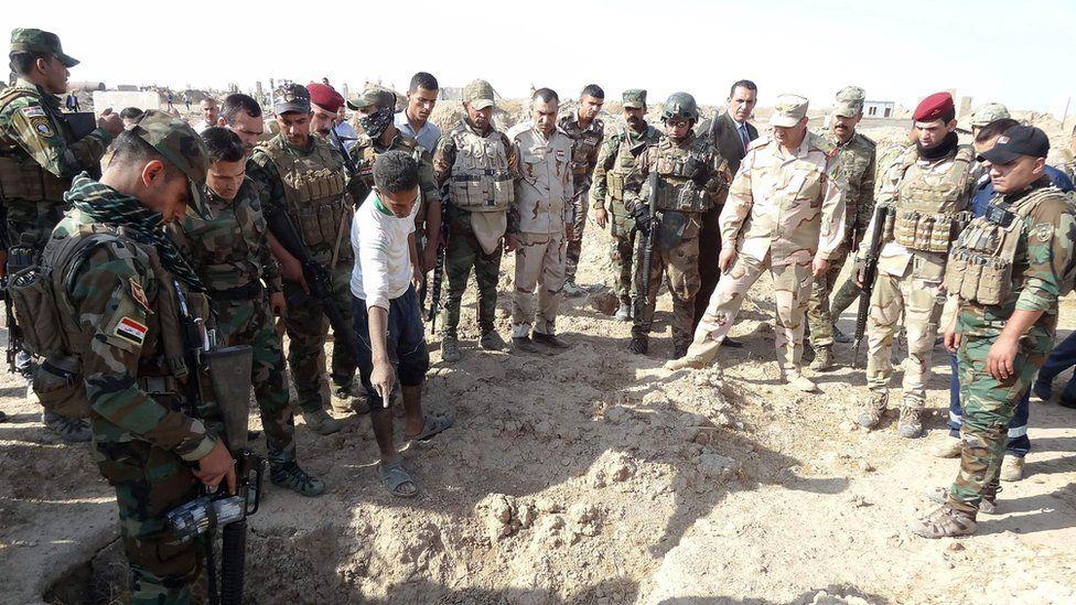 Iraqi forces inspect a mass grave near Hawija, 11 Nov 2017