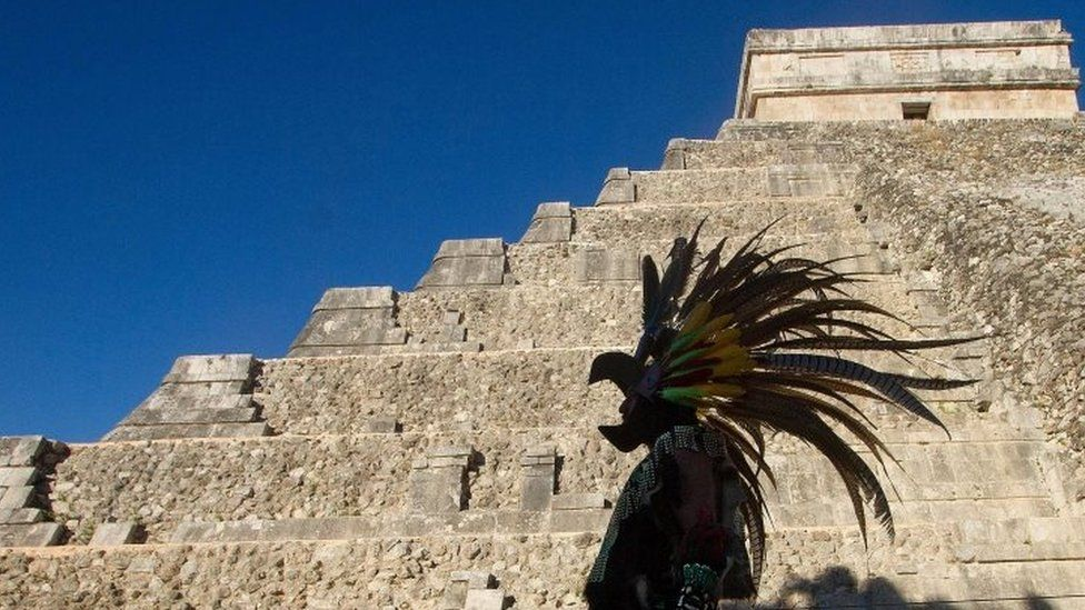 A Mexican man wearing a pre-hispanic costume walks next to the Kukulkan pyramid at the Chichen Itza archaeological park (20 December 2012)