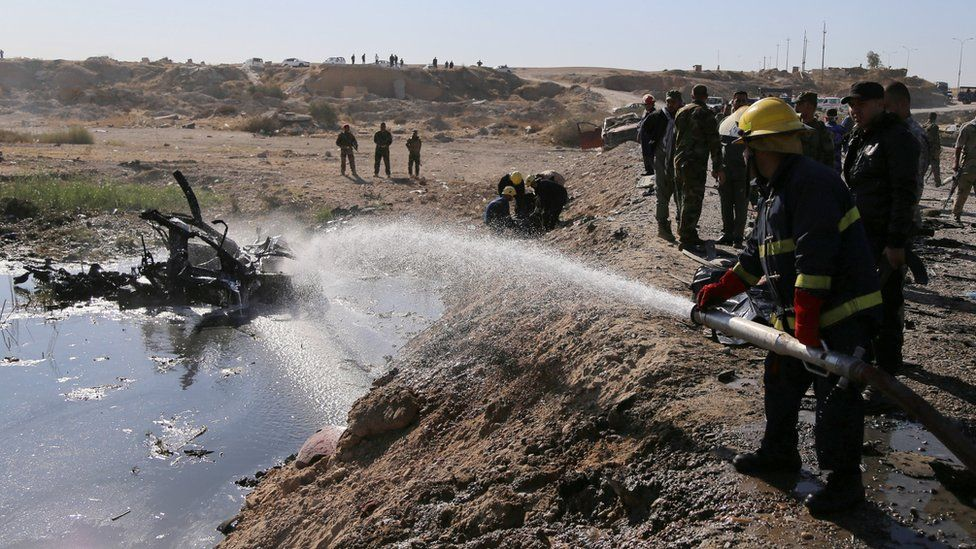 Firefighter hoses down remnants of suicide bomb blast near Tikrit on 6 November 2016