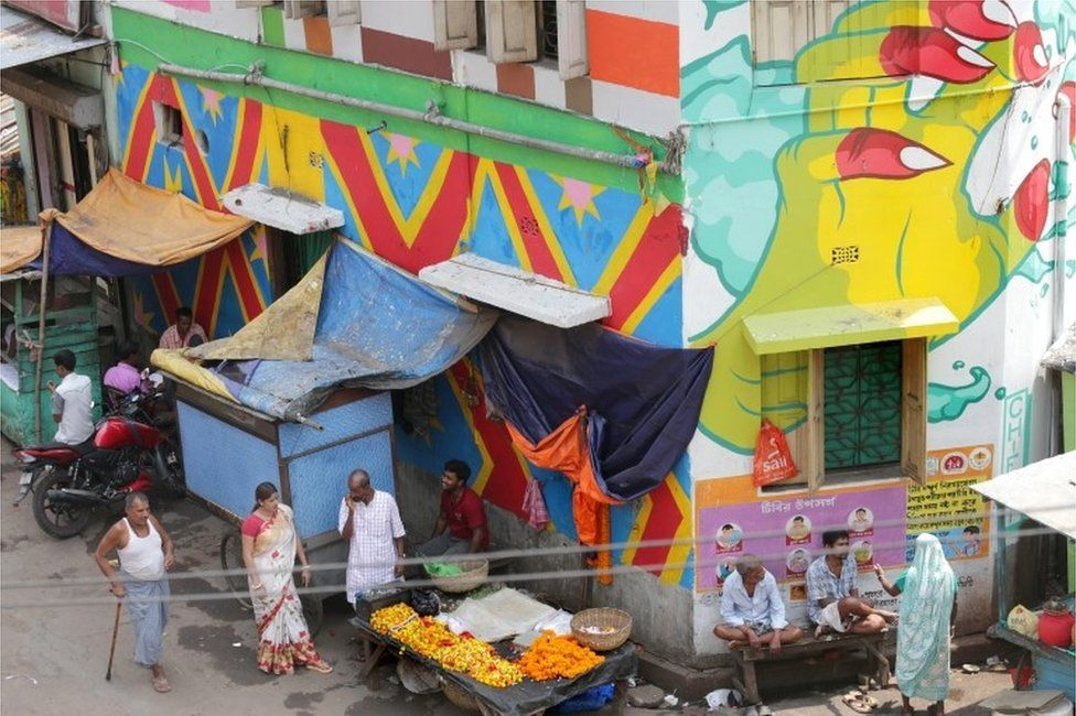 Indian commuters walk past a painted wall at Sonagachi red light district in Kolkata