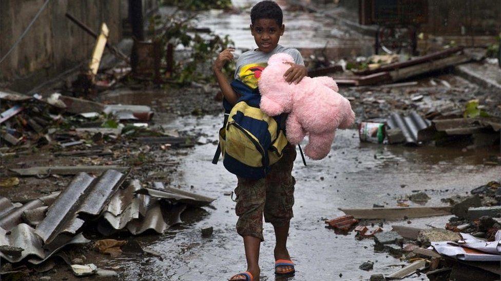 Boy carries his belongings through devastated Baracoa, Cuba, on 5 October 2016