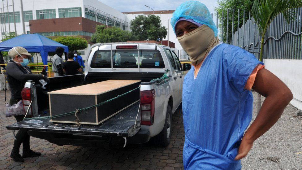 Man in protective kit to identify a relative in a morgue, Guayaquil, 15 Apr 20