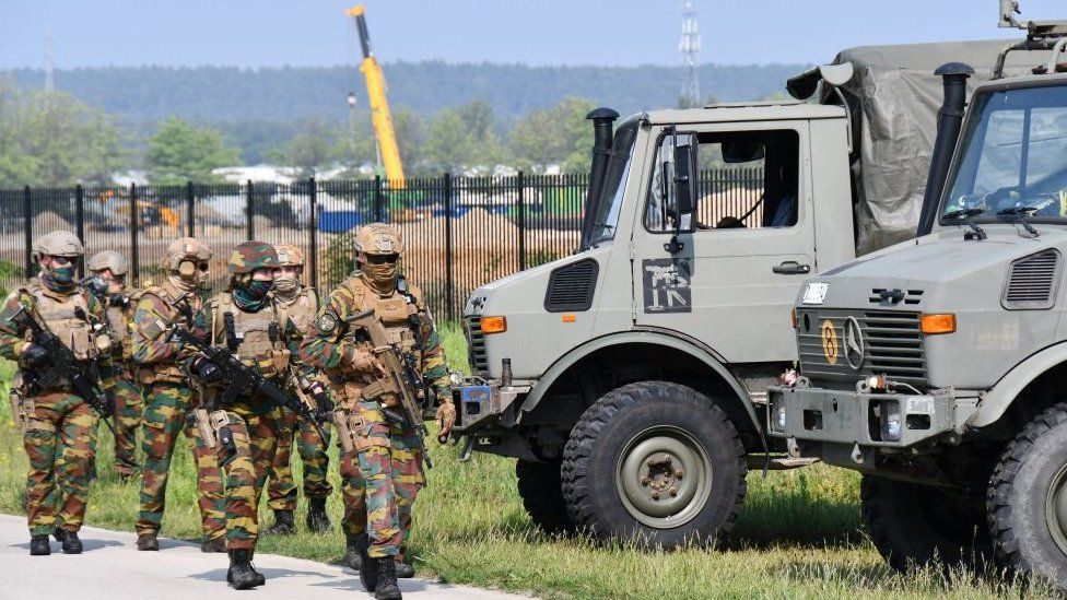 Heavily armed soldiers take part in an intensive sweeping of an area on the edge of the National Park Hoge Kempen in Maasmechelen on June 4, 2021, searching for Jürgen Conings