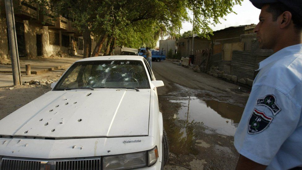 An Iraqi policeman stands by the bullet riddled car of two women shot dead by private security guards in Baghdad, 9 October 2007