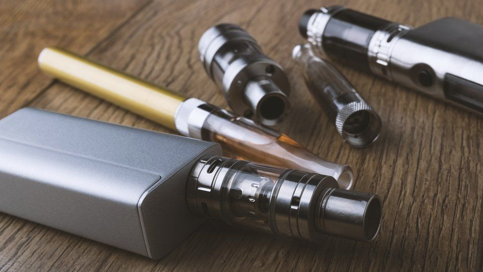 A vape pen and different components of an e-cigarette on a wooden background