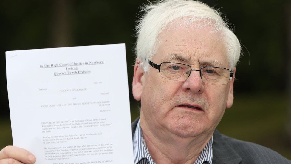 Michael Gallagher, who lost his son Aiden in the Omagh bombing, holds a writ in the Omagh Memorial Garden.