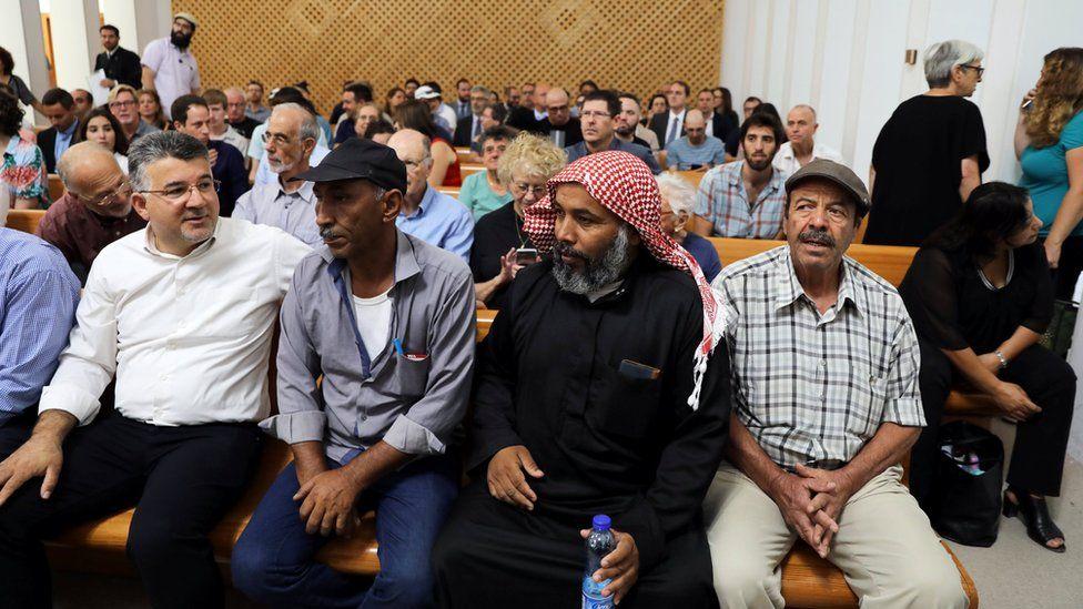 Residents of Khan al-Ahmar sit inside the Israeli Supreme Court building in Jerusalem on 1 August 2018