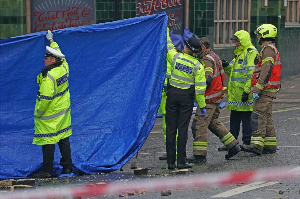 Police officers and firefighters erect tarpaulin