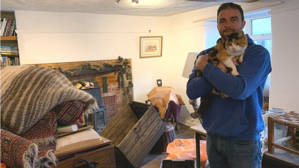 Griff Wyatt surveys the damage inside his home, while holding one of the family's cats