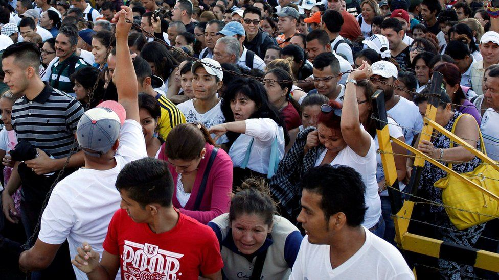 Venezuelan citizens push to each other trying to cross over the Simon Bolivar international bridge to Colombia to take advantage of the temporary border opening on 10 July