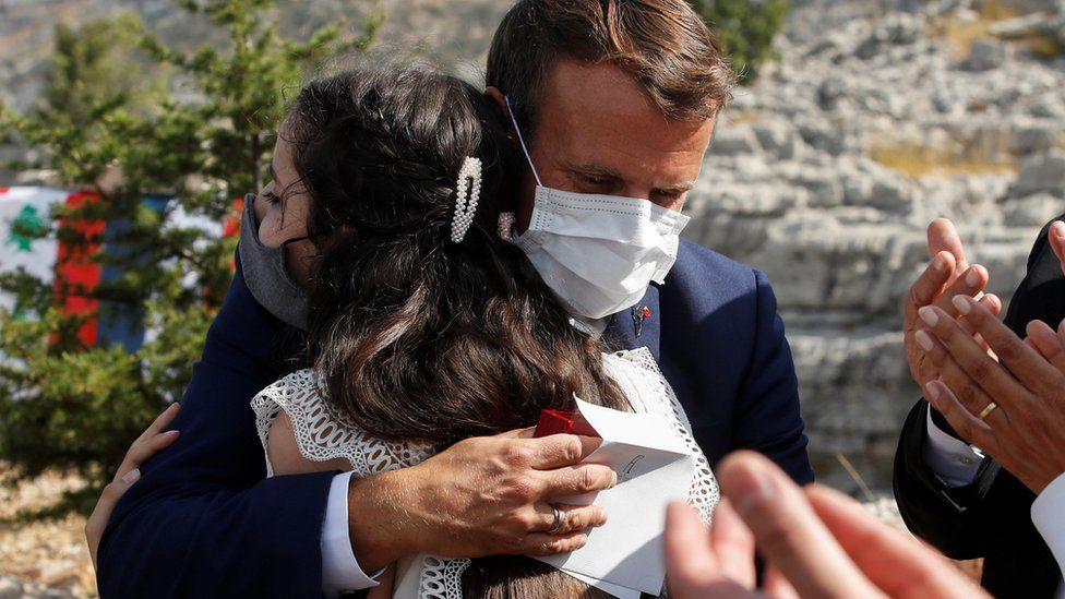 French President Emmanuel Macron hugs a victim of the Beirut blast after planting a cedar tree in Jaj, Lebanon (1 September 2020)