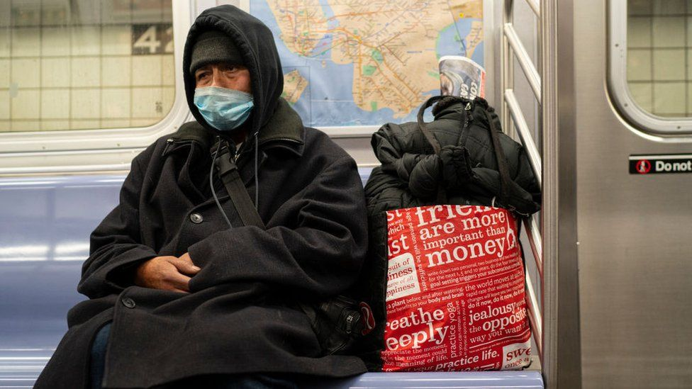 A homeless man carrying his belongings rides the subway December 30, 2020 in New York City. It is estimated that among New York City's nearly 80,000 homeless, there are every night 4,000 people sleeping on the the city's streets, in subways and in other public spaces
