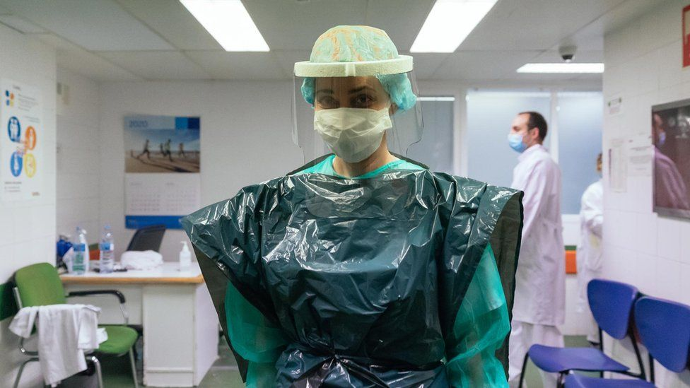 Also short of PPE, an intensive care nurse in Spain wears a bin bag and a protective plastic mask, donated by a local company.