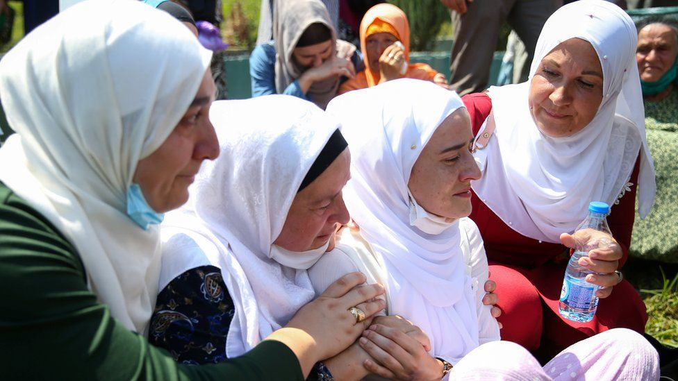 Women cry at a graveyard during a mass funeral in Potocari near Srebrenica