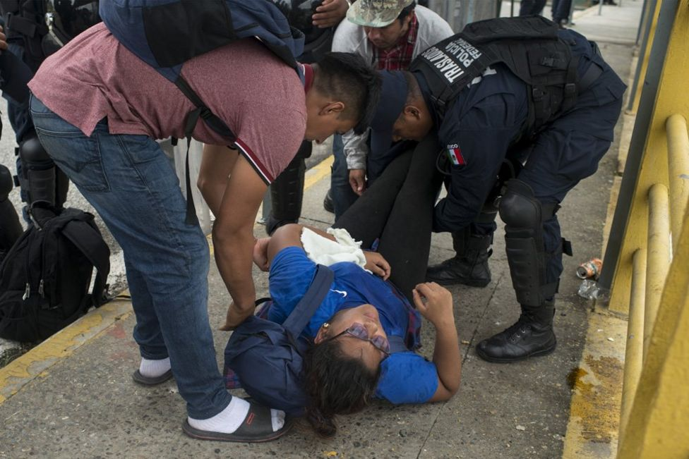A woman faints after walking for several days from Honduras on the crowded border bridge separating Guatemala and Mexico