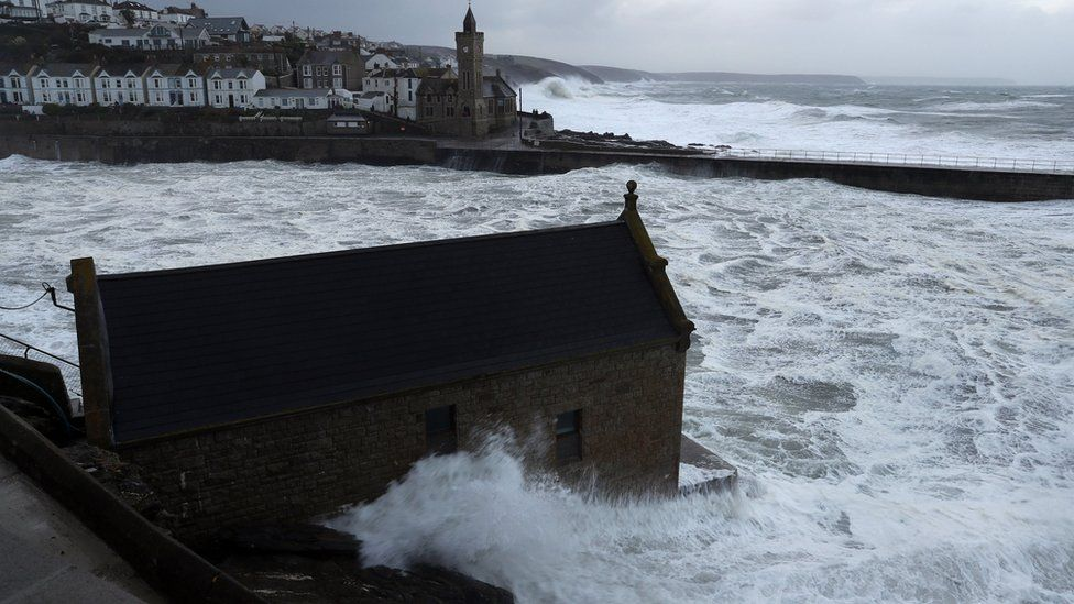 Waves crash into the seafront in Portlevenin, Cornwall
