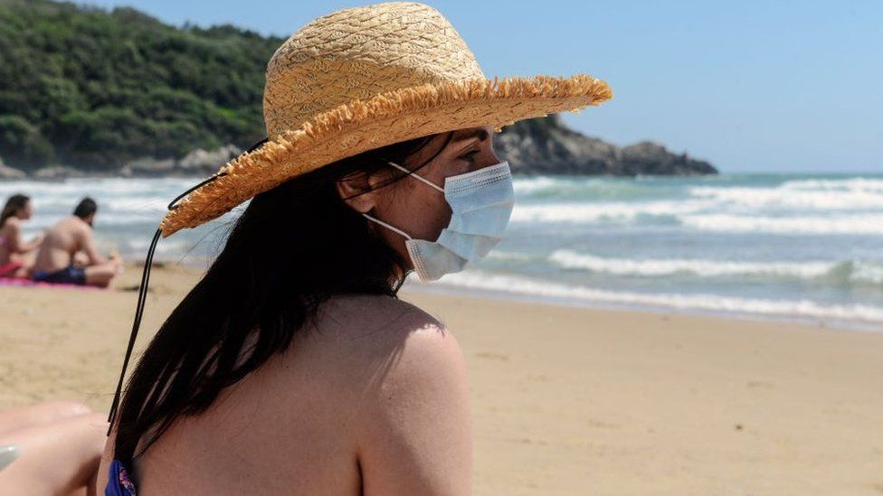 Woman on a beach wearing a face mask