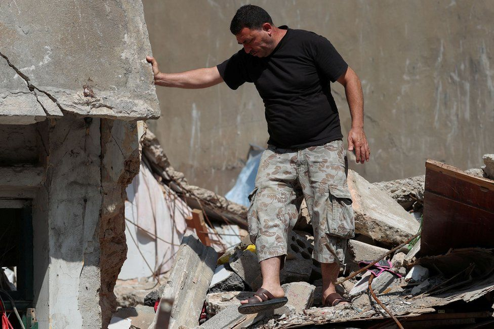 Syrian refugee Ahmed Staifi walks among the debris of a house were his wife and two of his daughters were killed following an explosion in Beirut, Lebanon (11 August 2020)