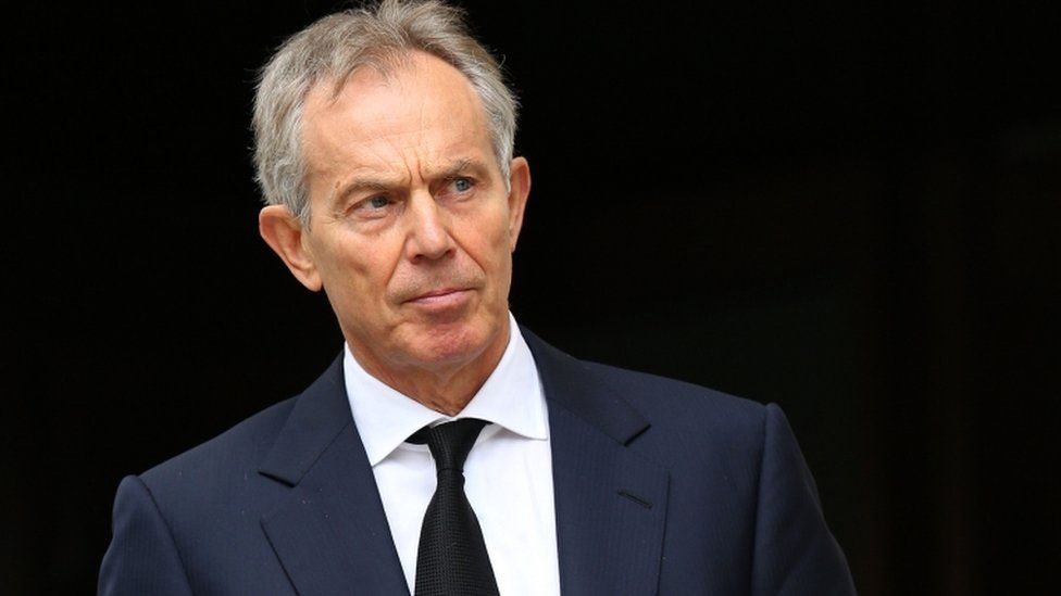 Tony Blair in front of a black background, in a photograph from 2012