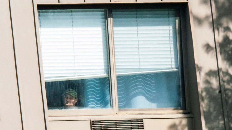 Man looks out window of facility