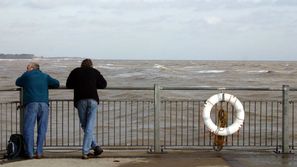 Two men looking over a fence towards the sea