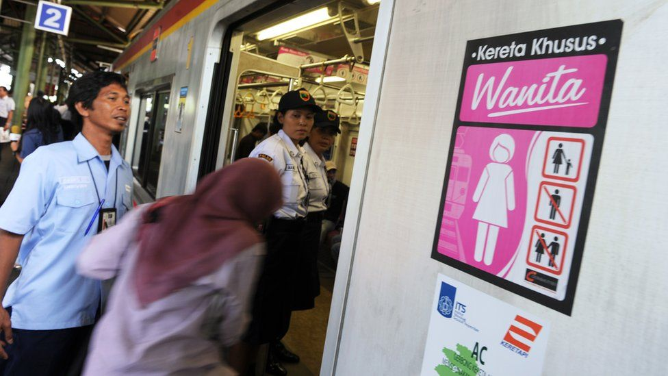 A passenger boards a women-only train coach of the state railway PT Kereta Api Indonesia at Jakarta station