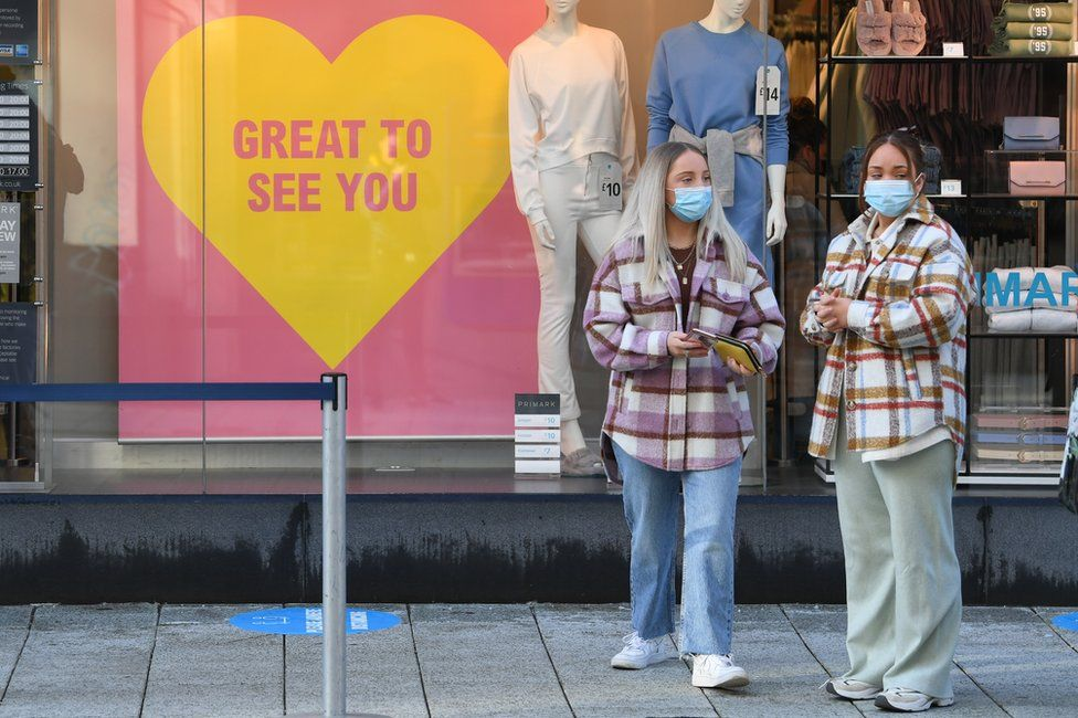 Two women wearing face masks stand outside Primark