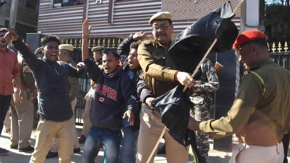 Assam Police personnel remove black flags from Krishak Mukti Sangram Samiti (KMSS) activists protesting with 69 other indigenous organizations of Assam during a demonstration against the Citizenship Amendment Bill 2016,