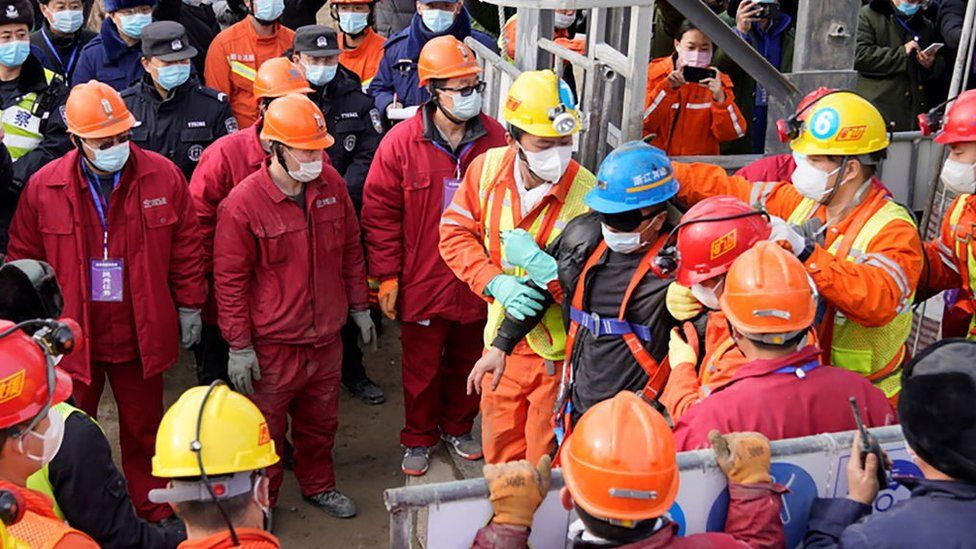 One (C-blue helmet) of twenty-two Chinese miners is saved from hundreds of metres underground where they had been trapped for two weeks after a gold mine explosion in Qixia, in eastern China's Shandong province on January 24, 2021.