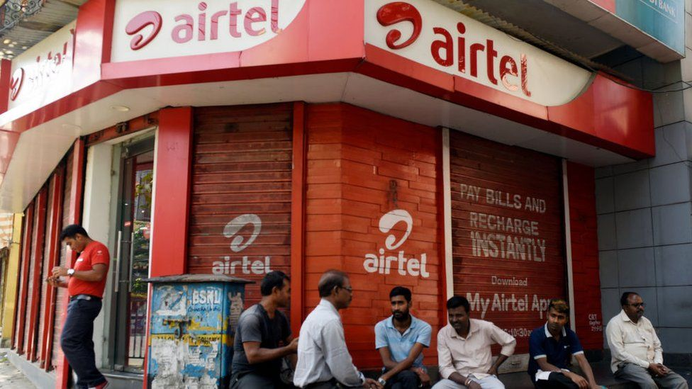 Men sit in front of Airtel store in Kolkata