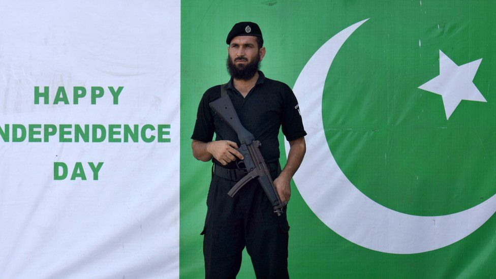 A Pakistani security official stands guard in front of the national flag on a road side as nation celebrate the Independence Day, in Peshawar, Pakistan, 14 August 2017