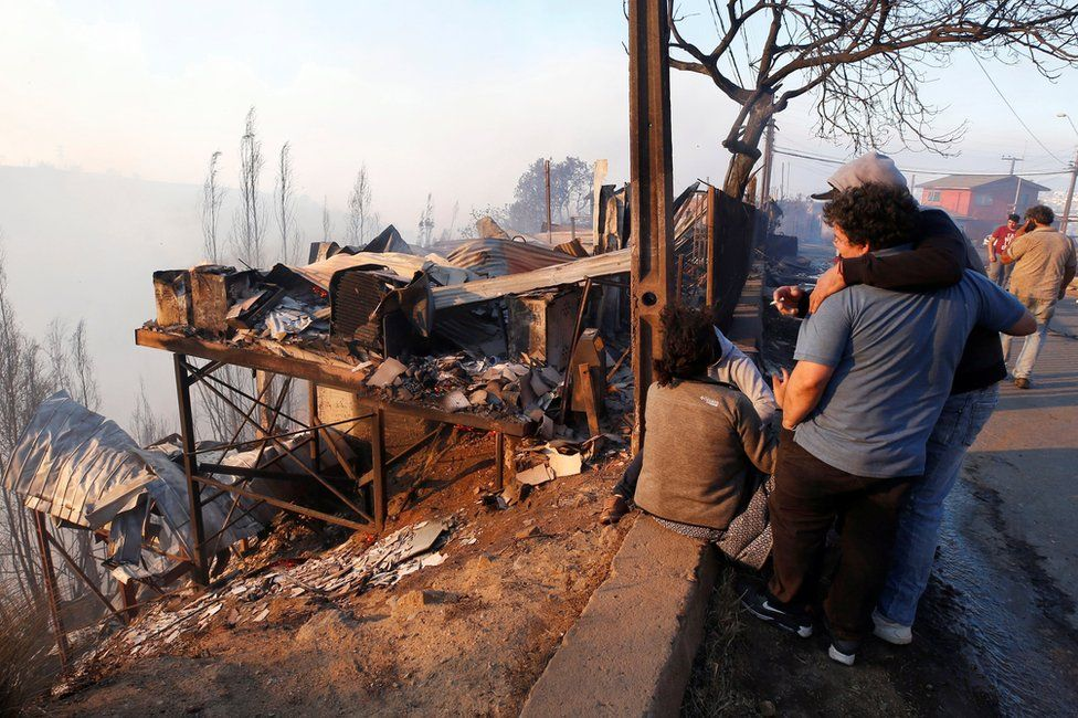 People react next to the debris of their house following the spread of wildfires in Valparaiso, Chile, 24 December 2019