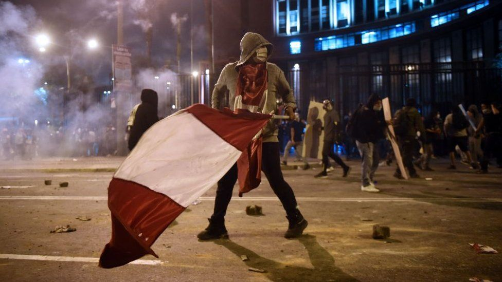 Protester carries a Peruvian flag during clashes in Lima on 14 November 2020