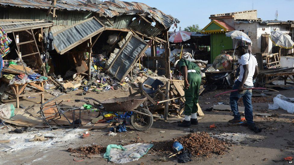 People gather at the site of a suicide bomb attack at a market in Maiduguri, Nigeria, 22 June 2015
