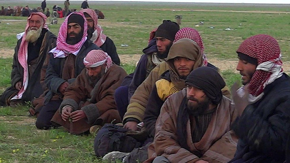 Militant men sit down with their heads covered