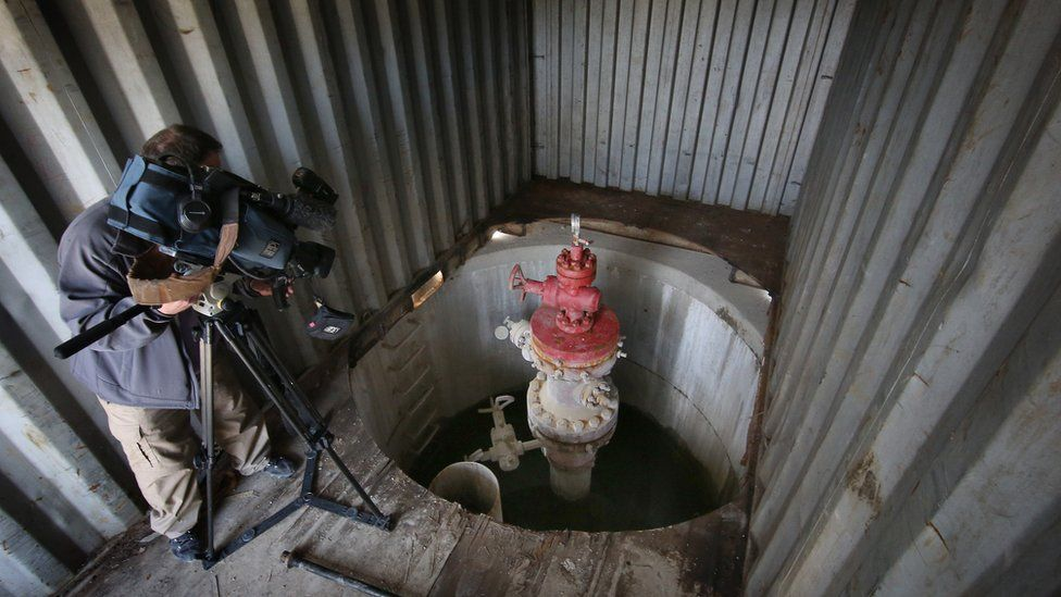 A cameraman films the well