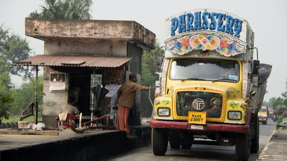 A lorry driver in his personalised hand-painted yellow Tata Semi-Forward Cab 1210SE Truck stops at a road toll in Kochi, Kerala, India.