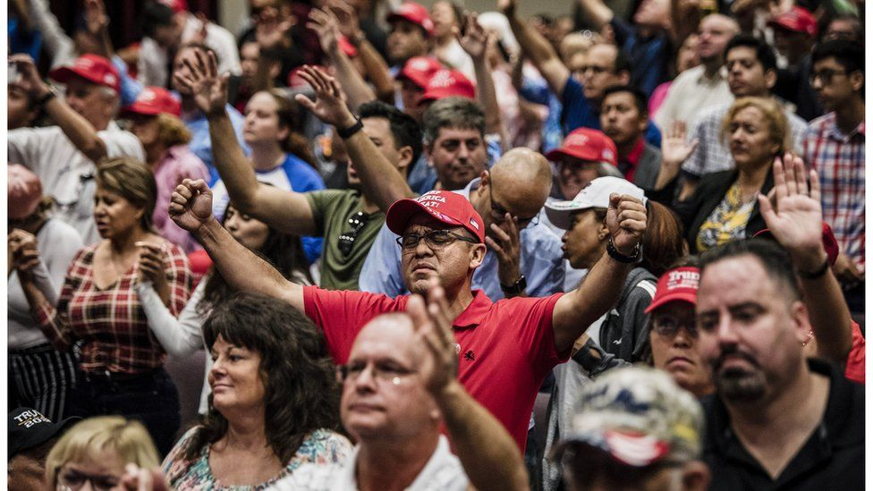 """Attendees pray together before President Donald Trump addresses the crowd at the King Jesus International Ministry during a """"Evangelicals for Trump"""" rally in Miami"""
