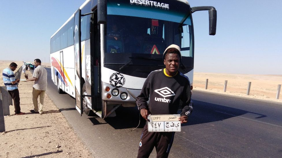 Alvin Zhakata holding up the licence plate of a coach in the desert en route from Sudan to Egypt