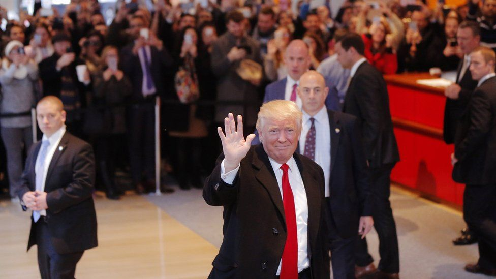 US President elect Donald Trump reacts to a crowd gathered in the lobby of the New York Times building after a meeting in New York, U.S., November 22, 2016