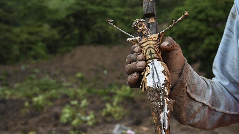 A man shows a Christ found in the mud after a landslide