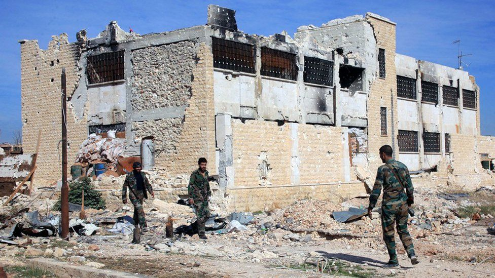 Syrian government troops walk inside the Kweiras air base, east of Aleppo, Syria