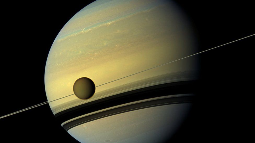 Saturn and its moon Titan. Titan's atmosphere is a featureless brown.