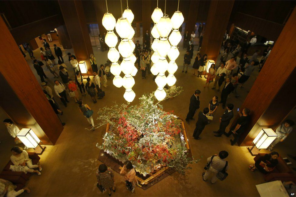 Visitors stand at the main lobby of Hotel Okura in Tokyo, Monday, 31 August 2015