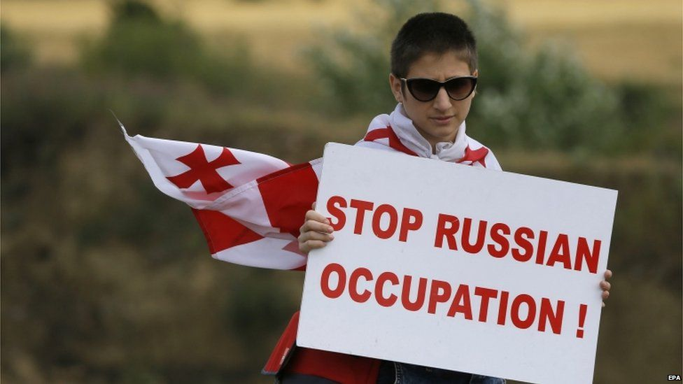 "A Georgian protester holds a placard reading ""Stop Russian Occupation"" during an anti-Russian rally near the border between Georgia and the breakaway region of South Ossetia, 14 July 2015"