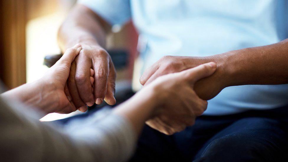 Carer holding patient's hands